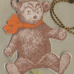 Invitation in shape of brown cardboard bear with a red handkerchief around its neck.