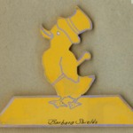 """Flat, yellow wooden cutout of a duck wearing a top hat and holding a cane, """"Barbara Shields"""" is handwritten at the bottom and there is a blue outline surrounding the object."""