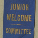Blue ribbon badge with pin for members of the Junior Welcome Committee.