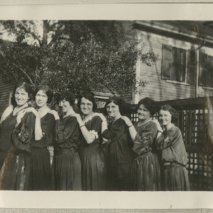 Photograph of seven women with hands on each others shoulders in front of a house and trees