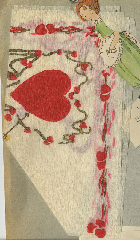 A folded napkin depicting a heart, probably from the Valentine's Day party mentioned in the adjacent card's caption. Unfolded dimensions indeterminable because it is glued together.