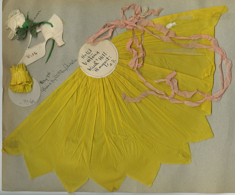 "Yellow tissue paper fan with pink tissue paper strings that once held a balloon (small piece of balloon still attached). White circular paper sewn to fan has caption: ""Hotel Victoria Kent's Hill Banquet '23."""