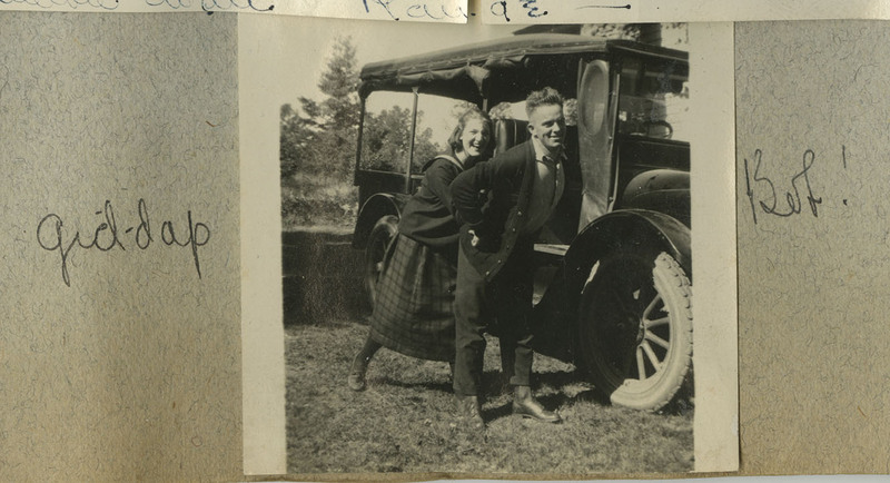 "A photograph of a young couple in front of a car. Captions: ""Gid-dap"" and ""Bob!"""