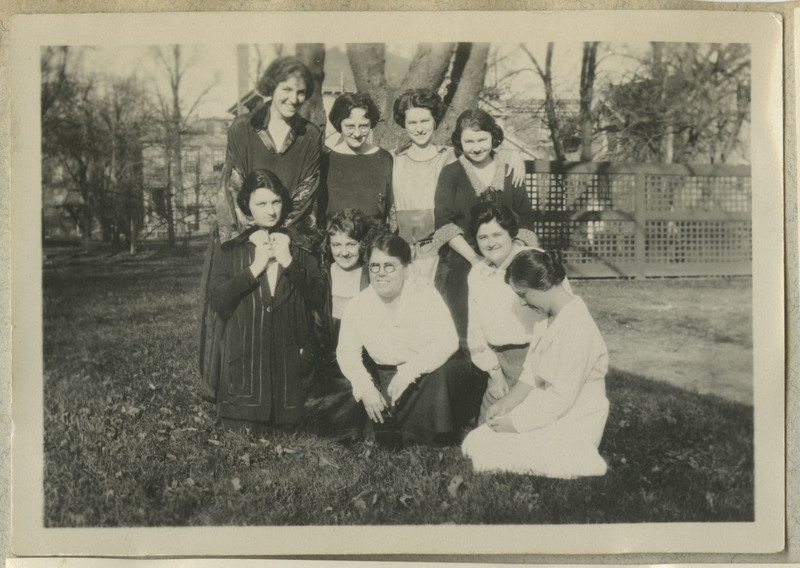 Photograph of nine women, five kneeling and four standing behind them. Six are smiling.