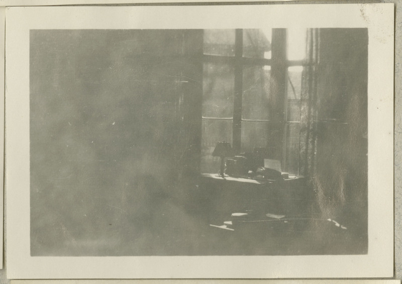 Faded photograph of a room with sunlight coming through a window. There is a lamp in front of the window.