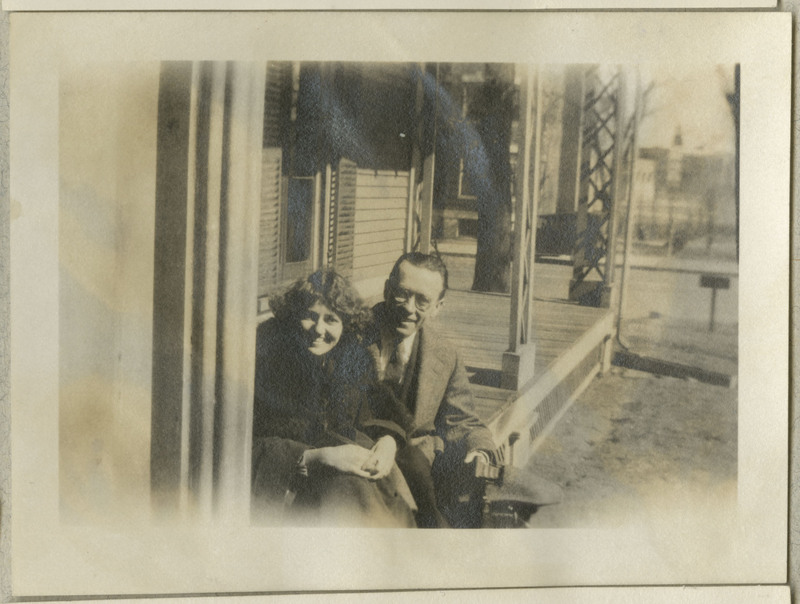 Faded photograph of man and woman smiling on a porch.