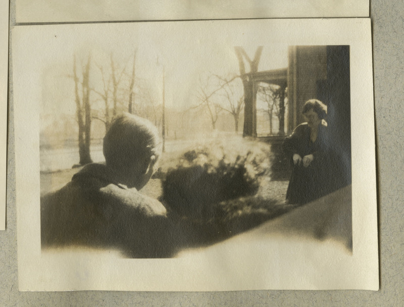 Small photograph of man and woman outside showing the back of the man's head.  It is very sunny.  The woman is wearing a coat.  The photograph is faded.