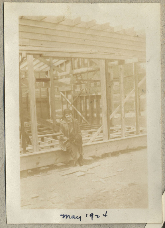 "A faded photograph shows a woman sitting in the wooden frame of a building that is under construction, holding her hat in her hands. The woman may be Ruth. Caption: ""May 1924"""