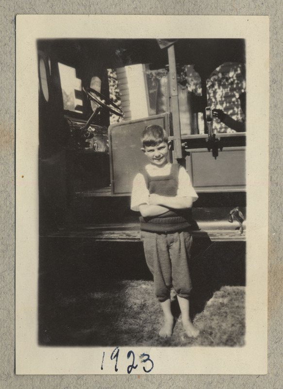 "A young child stands, smiling, with arms crossed, in front of a vehicle. Caption: ""1923"""