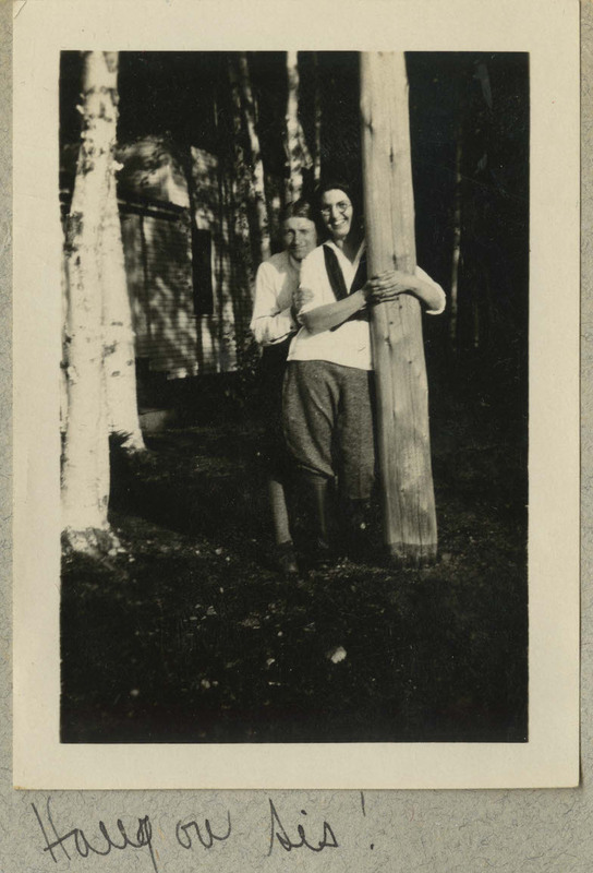 "The photograph depicts a man and a woman standing next to a tree. The man is holding onto the tree with both arms. Caption: ""Hang on, Sis!"""