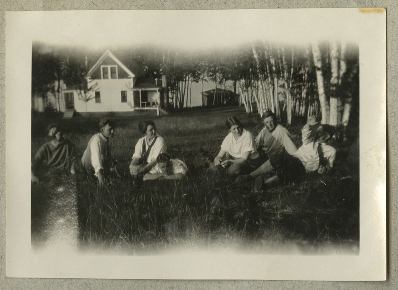 The photograph depicts seven people sitting in front of what appears to be a lakehouse, a cabin on the lake, and a forested area.