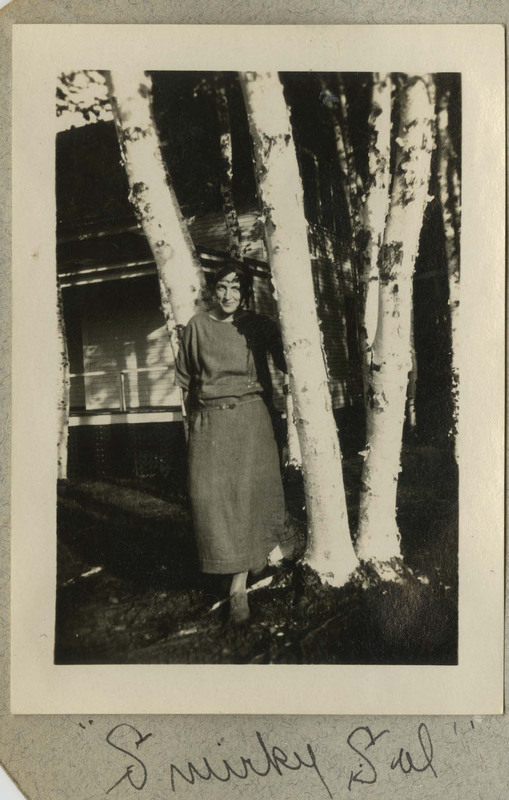 "The photograph depicts a woman standing next to several trees, with some kind of house or cabin in the background, likely Ruth Gates. Caption: ""Smirkey Sal."""
