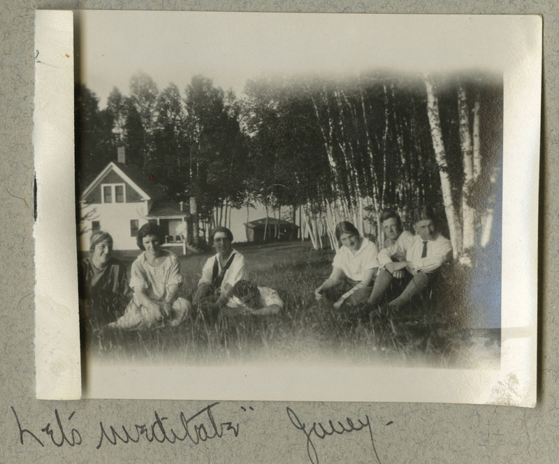 "The faded photograph depicts seven people sitting in front of a house with trees also visible in the background.  Caption: ""Let's meditate, Jenny!"""