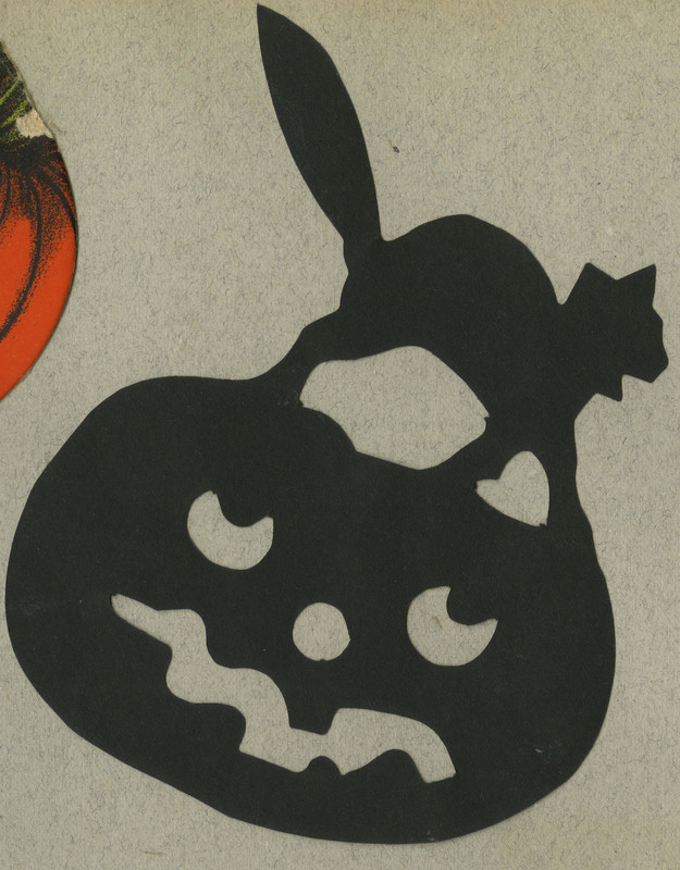 Paper decoration depicting the likeness of a cat standing on top of a jack-o-lantern.