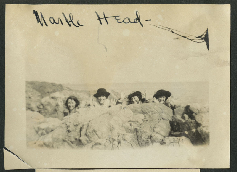 "Photograph likely of Ruth Dorcas Gates (second from the left) and three friends waving from behind a rocky outcropping on a beach in Marblehead, MA. All are dressed in coats. Front Transcription: ""Marble Head-"" Partial back Transcription:""Pruitt / Pruitt. / Gladys Swiegart[?] / sister altitude[?] / school in city g. / last yr."" This transcription represents only the right half of the photograph since the left is still glued to the original page. The word altitude is a guess, as much of this word is obscured by the number 442 written over the top of it."