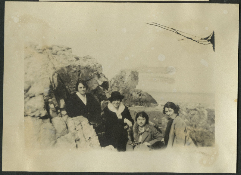 Photograph of likely Ruth Dorcas Gates (second from the left) and three friends pose on rocks by the sea  in Marblehead, MA.  The woman to the right of Ruth is sitting, all others are standing. There are two tall outcroppings of rock, one supporting the leftmost woman and one in the distance behind the women.