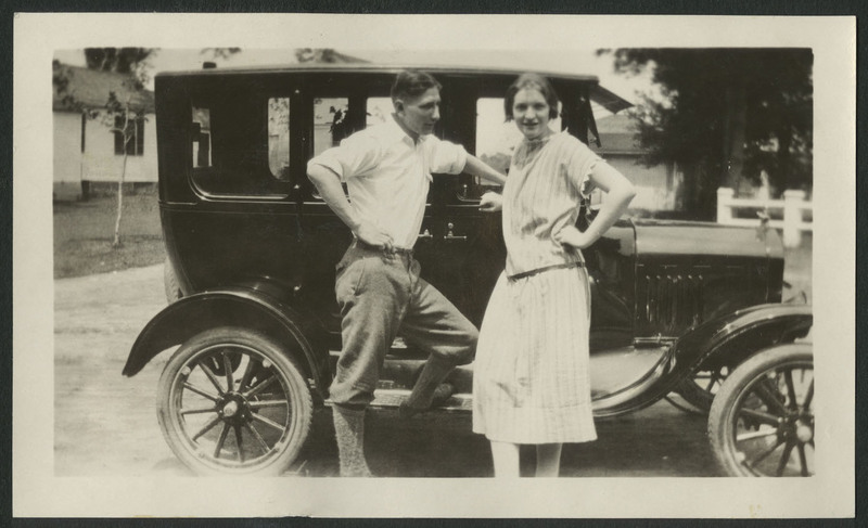 Man and woman, possibly Ruth Gates, leaning on car parked in front of houses