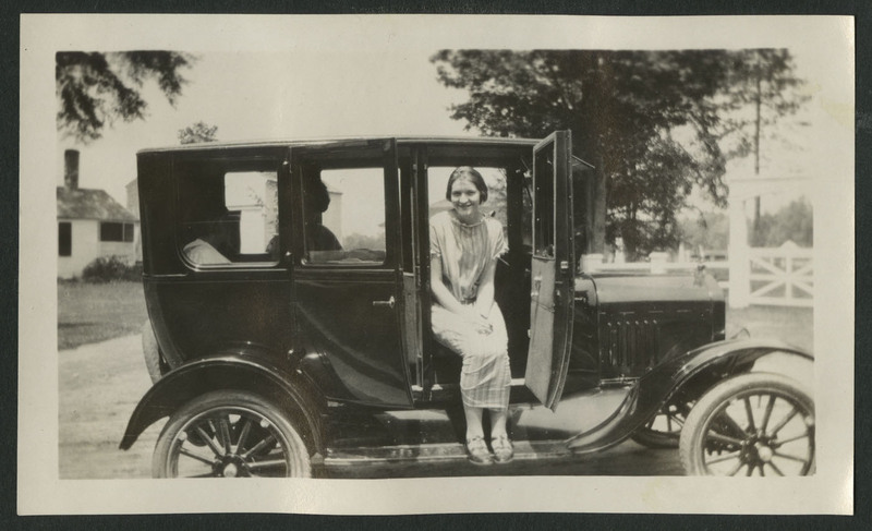 Two women, one possibly Ruth Gates, seated in car parked in front of houses