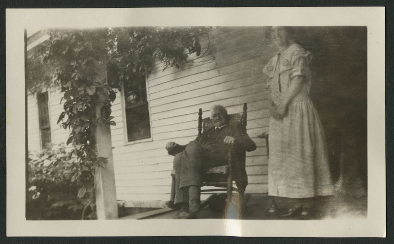 Woman standing next to an older man seated in a rocking chair on a porch with garden visible in corner