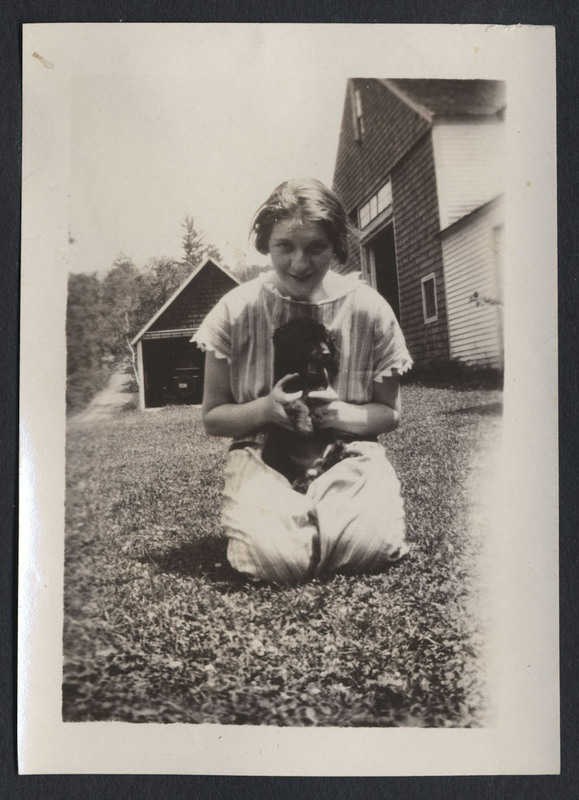 A photograph of an unknown woman kneeling in the grass. She is holding a dog, its breed is unknown.